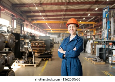 Happy young female worker of large modern factory in blue uniform and protective helmet crossing her arms on chest