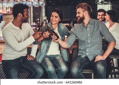 Happy young friends in casual clothes are  smiling and clinking bottles of alcoholic beverage while sitting at bar counter in pub.