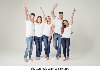 Happy Young Friends in Casual White Shirt with Copy Space and Blue Jeans, Raising their Arms and Smiling at the Camera on White Background.
