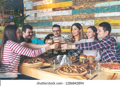 Happy young friends celebrating by toasting with beer eating pizza and burgers at pub restaurant - Friendship concept with young people enjoying time together and having genuine fun at rustic pizzeria