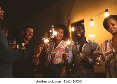 Happy young friends celebrating new year eve with sparklers fireworks and drinking cocktails on patio house party - Youth people lifestyle and holidays concept