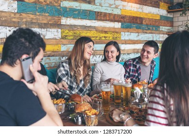 Happy young friends celebrating with pizza burgers and drinking beer at bar restaurant - Friendship concept with young people enjoying time together and having genuine fun at rustic pizzeria