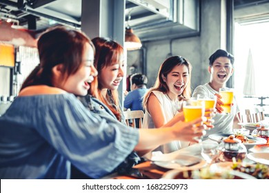 happy young friends dining and drinking beer at restaurant