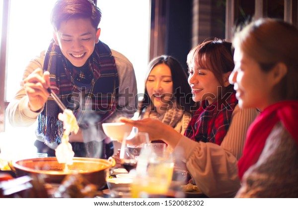 happy young friends eating hot pot in restaurant at winter