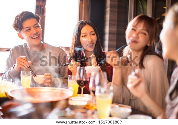 happy young friends enjoy dinner in hot pot restaurant