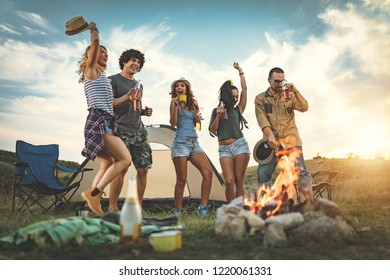 Happy young friends enjoy a nice day in nature. They're holding beer bottles, laughing, dancing, and talking happy to be together.