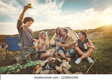 Happy young friends enjoy a nice day in nature. They're grilling sausages, eating, drinking  champagne, laughing and talking happy to be together.