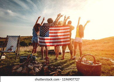 Happy young friends enjoy a sunny day in nature. They're looking at sun holding american flag and greeting, happy to be together.