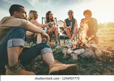 Happy young friends enjoy a sunny day at the mountain. They're laughing and toasting with beer bottles by the bonfire near tent.