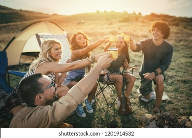 Happy young friends enjoy a sunny day at the mountain. They're laughing and grilling -roasting sausages on sticks over a campfire near tent.