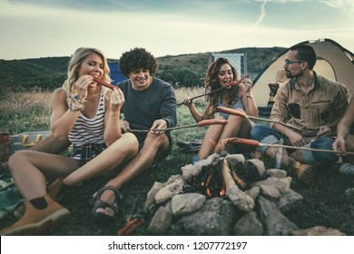 Happy young friends enjoy a sunny day at the mountain. They're laughing and roasting sausages on sticks over a campfire near tent.