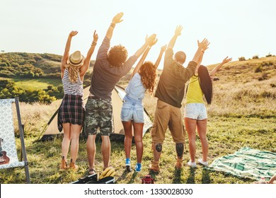 Happy young friends enjoy a sunny day in nature. They're looking at sun and greeting, happy to be together.
