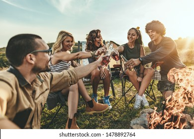 Happy young friends enjoy a sunny day at the mountain. They're laughing and toasting with beer bottles by the bonfire happy to be together.