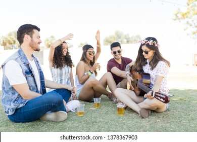 Happy young friends enjoying music while having beer on field during summer