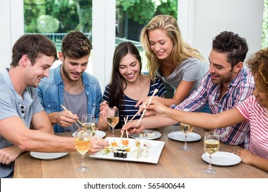 Happy young friends enjoying wine and sushi at home