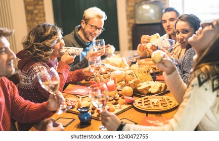 Happy young friends group tasting christmas sweet food diner having fun at home wine party - Winter holidays concept with millenial people enjoying new year's eve supper eating together - Warm filter