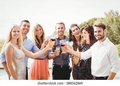 Happy young friends having drinks at swimming pool and enjoying holiday