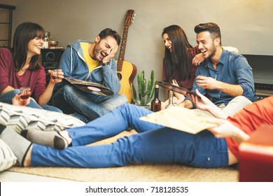 Happy young friends having fun at home listening vintage vinyl disc music in living room - Group of people enjoying their time in apartment drinking shots and laughing