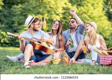 Happy young friends having picnic in the park.They are all happy,having fun,smiling and playing guitar.