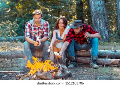 Happy young friends having picnic. Group of friends enjoying picnic in the forest. Happy friends on a camping trip relaxing by campfire. Company friends picnic or barbecue near bonfire