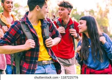 Happy young friends hiking with positive attitude - Cheerful group of teenagers smiling looking at each other holding trek backpack - Concept of friendship, travel and outdoor activity - Focus on girl