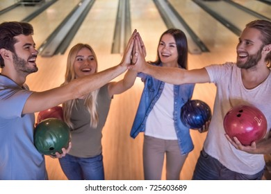 Happy young friends are holding balls, giving high five and smiling while playing bowling together