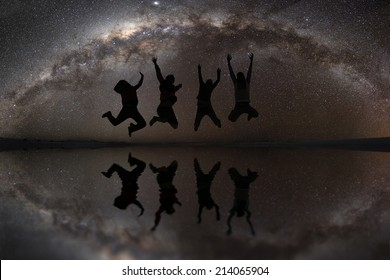 Happy young friends jumping under starry sky in Solar de Uyuni, Bolivia
