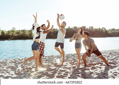 happy young friends playing volleyball on sandy beach at daytime