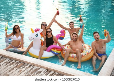 Happy young friends with refreshing cocktails relaxing in swimming pool