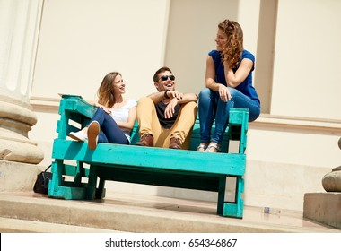 Happy young friends sitting on big bench outdoors at summertime.