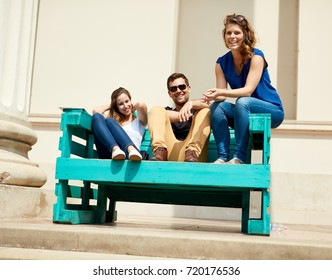 Happy young friends sitting on bench outdoors.