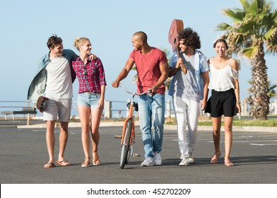 Happy young friends walking in a row. Group of smiling multi ethnic guys and girls walking while holding cycle, guitar and skateboard. Happy young couples enjoying with friends.