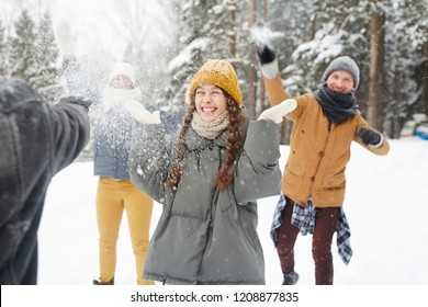 Happy young friends in winter coats having snowball fight in forest: excited girl standing in center and feeling snow on face