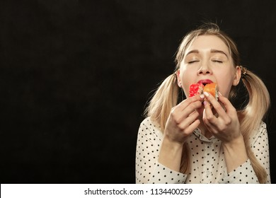 happy young fun woman eats sushi on black background with copy space