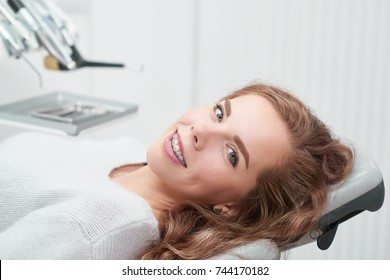 Happy young ginger haired woman with braces smiling to the camera sitting in a dental chair at the clinic waiting for examination copyspace positivity healthcare medicine dentistry people smile.