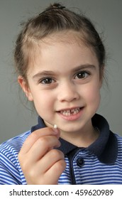 Happy young girl (age 6) holds her first falling milk teeth, looking at camera. Childhood healthcare concept. Real people. Copy space