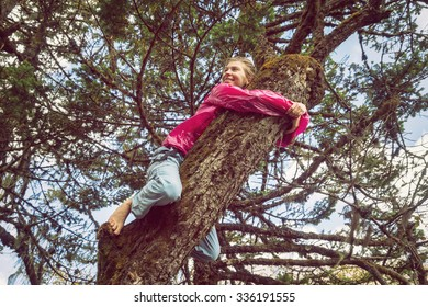 A happy young girl with bare feet climbing a tree