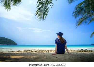 happy young girl with blue dress, sitting on the beach at the tropical island beach with clear blue sky