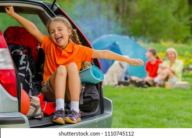 Happy young girl in car near his camp tent at green field