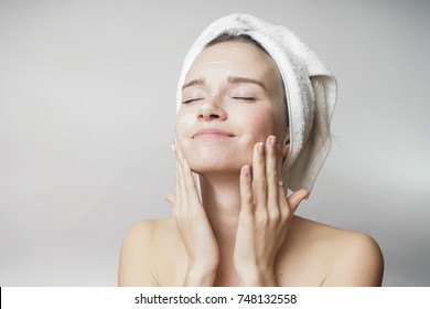 happy young girl with clean skin and with a white towel on her head washes face