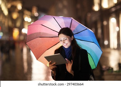 Happy young girl with colorful umbrella using tablet computer outdoor. She standing in the city street in the rainy evening