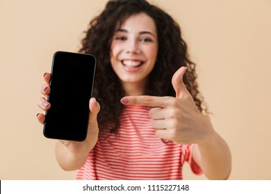 Happy young girl with dark curly hair showing blank screen mobile phone and pointing finger isolated over beige background