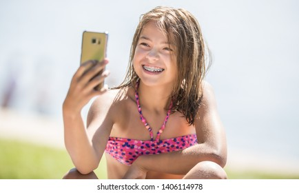 Happy young girl with dental braces making selfhie on beach in summer hot day.