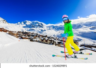Happy young girl enjoying winter vacations in mountains, Val Thorens, 3 Valleys, France. Playing with snow and sun in high mountains. Winter holidays.