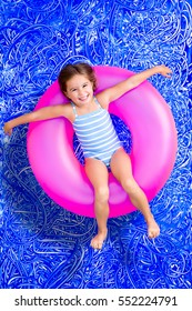 Happy young girl floating in a summer pool on a colorful pink plastic ring looking up at the camera with a lovely friendly smile, conceptual image on blue painted water background with ripples