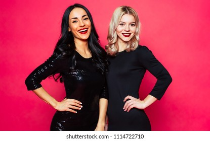 Happy young girl friends in dress hugging each other on pink background