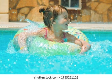 Happy young girl having fun in the water and enjoys summer vacation in the pool. Happy carefree childhood concept.