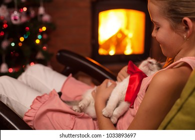 Happy young girl with her christmas present - a kitten, relaxing in front of the fireplace in holidays season, shallow depth