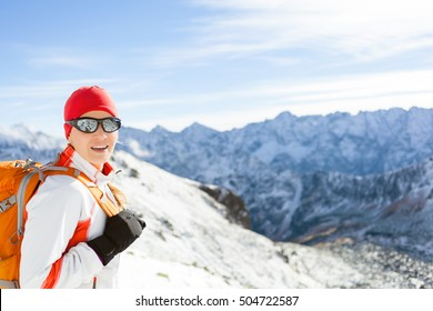 Happy Young Girl Hiking in Winter High Mountains with Backpack. Fitness and healthy lifestyle outdoors in white winter inspirational beautiful nature landscape, Tatra Mountains in Poland.