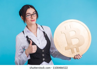 happy young girl holding golden bitcoin, winking, thinking about crypto currency.